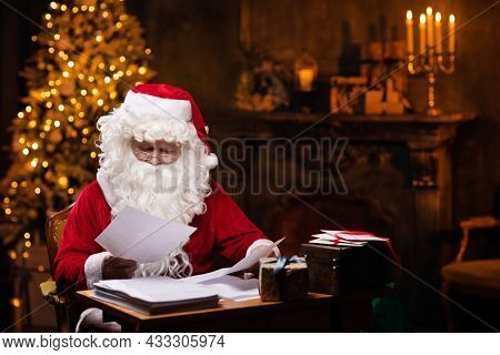 Workplace of Santa Claus. Cheerful Santa is reading letters from children while sitting at the table. Fireplace and Christmas Tree in the background. Christmas concept.