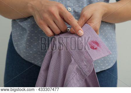 Woman Pointing At Lipstick Kiss Mark On Her Husband's Shirt, Closeup