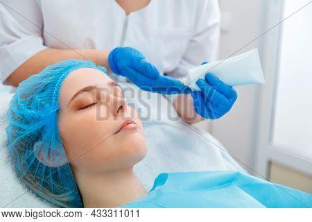 Beautician Do Beauty Procedure For Woman Client. Beautician Doctor Dermatologist Apply Moisturizing