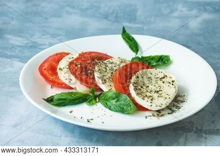Traditional Italian Salad With Ripe Tomatoes, Mozzarella Cheese With Fresh Basil Leaves