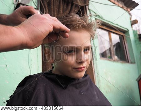 A Blond Boy Of 8 Years Old Gets His Hair Cut With Scissors. Hairdresser Services At Home. Haircut Fo