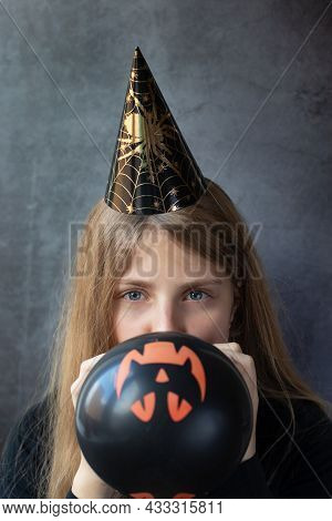 Happy Smiling Girl In A Halloween Paper Cap Inflating Black Ball For Halloween. People, Halloween, D