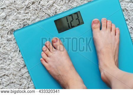 Children's Legs On The Scales. Weighing And Control Of Body Weight Parameters. Close-up. View From A