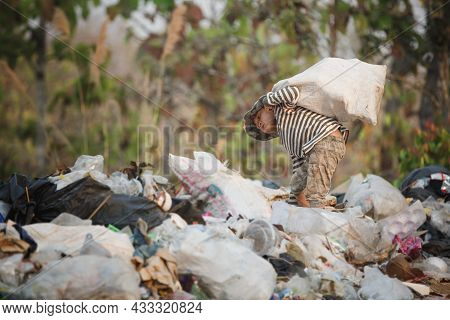 A Poor Boy Collects Trash To Sell. Life And Way Of Life Of The Poor Concept Of Child Labor, Poverty,