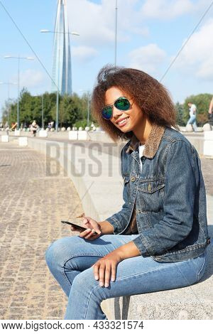Beautiful afro american woman using mobile in the street. Communication and lifestyle concept.