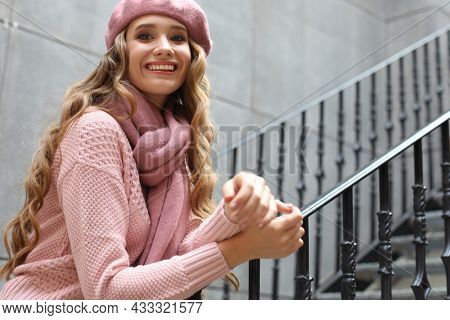 Young beautiful woman stands by the stairs