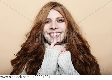 Emotional young woman smiles and touches her face. Happiness and joy. Lifestyle and people concept.