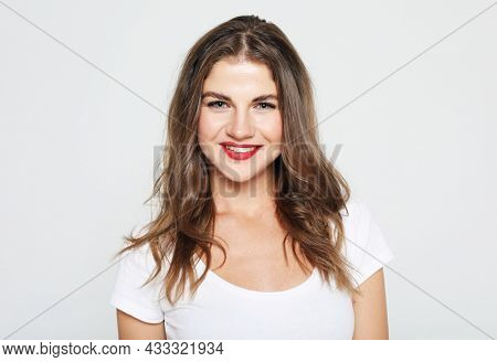 Lifestyle, emotion and people concept: Young cute smiling blond girl over grey background