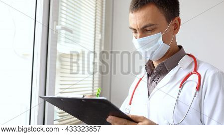 A Doctor Writing Patient Notes On A Medical Examination Or Prescription.