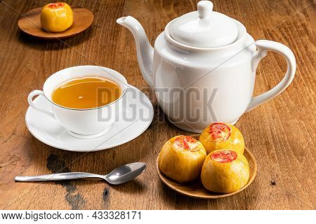 View Of Sweet Chinese Pastry Or Moon Cake Filled With Sweet Mung Bean Paste And A White Ceramic Cup