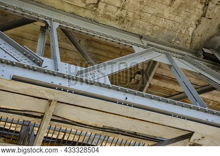 Metal Structures Under The Bridge, Large Metal Bridge Over Water. View From Under Metal Bridge. Meta