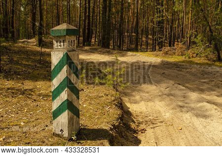 A Striped Border Post In The Forest With A Plot Number. Forest Road. Quarter Pillar In The Forest. A