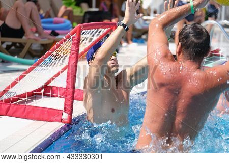 Young Men Playing Water Polo And Scoring Goal In Swimming Pool