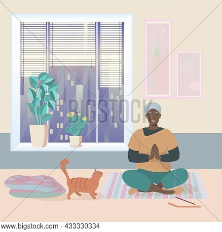 An Elderly African-american Woman Meditates At Home Against The Background Of A Large Window. Evenin