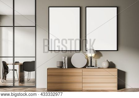 Two Canvases On The Beige Wall Of The Living Room Area With A Modern Sideboard. A Dining Room Behind
