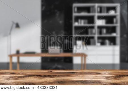 Office Room Interior With Laptop, Comfortable Armchair, Desk, Books, Folders, Bookshelf And Concrete