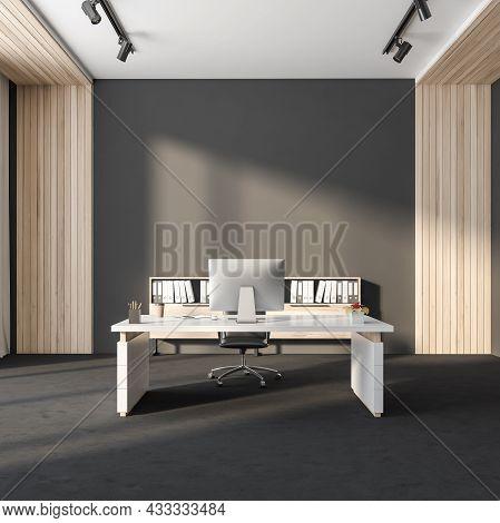 Dark Office Room Interior With Empty Grey Wall, Desktop, Armchair, Desk, Bookshelves And Concrete Fl