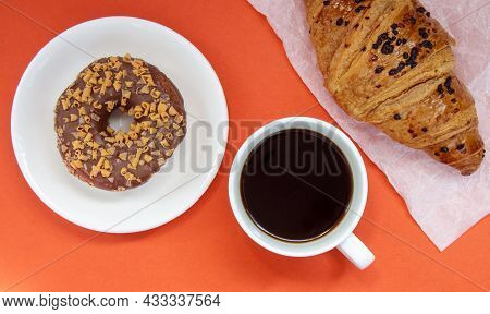 One Chocolate Donut, Croissant And Black Americano Coffee Without Milk In A White Cup On A Bright Ba