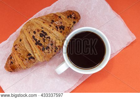Black Coffee Without Milk In A White Cup And A Chocolate Croissant On Parchment And Bright Backgroun