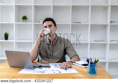 Young Businessman Sitting In The Office With A Laptop, Taking A Hot Coffee Break While Checking Docu
