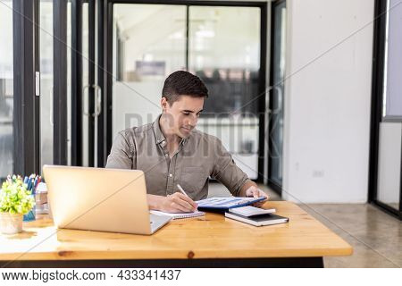 Young Businessman Sitting In The Office With Laptop, He Is Checking Documents From The Finance Depar
