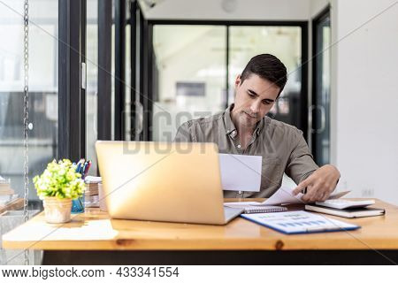 Young Businessman Sitting In The Office At His Company, He Is Checking The Correctness Of Company Fi