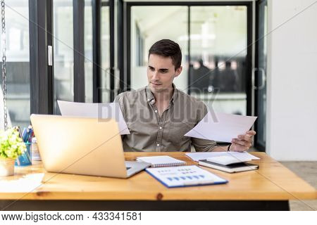 A Businessman Holding A Sales Document That The Sales Department Summarizes, He Looks Displeased Whe