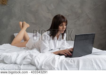A Freelancer Woman Lying In The Bedroom In The Morning On The Bed Works Online At A Distance With A