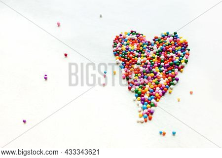 Vibrant Colorful Sugary Sprinkles Formed In A Heart Shape With Some Random Scatter Lay On Bright Whi
