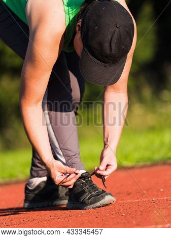 Middle Age Woman Stopped To Tie A String While Running In The Stadium. Black Hair Woman Runner Tying