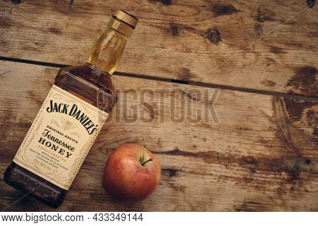Bottle Of Jack Daniels Honey And Apple At Weathered Wooden Table. Illustrative Editorial