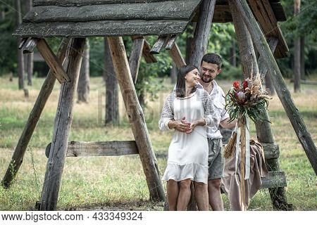 Young Man And Woman Smartly Dressed Hugging In The Forest With A Bouquet Of Exotic Flowers, Romance