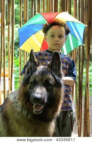 The caucasian boy and his huge dog stand near bamboo curtain in summer, there is a hat in the form of an umbrella at the child's head, his dog is the German Shepherd dog poster