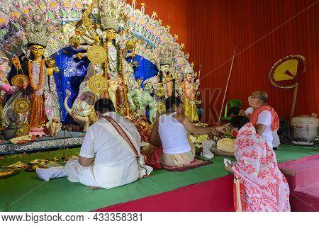Howrah, West Bengal, India - 25th October 2020 : Hindu Purohit Putting Tilak On Masked Female Hindu
