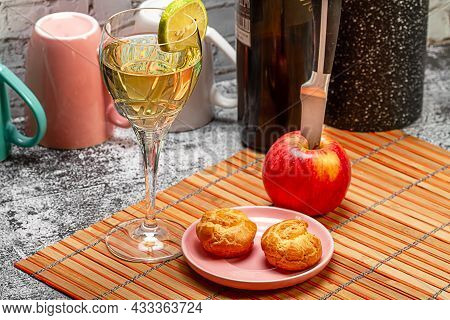 A Glass Of Wine With Lemon, A Saucer Of Eclairs And A Knife Stuck In Apples On The Kitchen Table. Ph