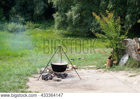 Old Cast-iron Cauldron On A Fire. Cooking Food Outdoors In A Pot On A Tripod. Ax In A Wooden Stump.