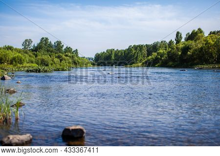 Fast-flowing Wide And Full-flowing Mountain River. The Shore Is Visible Against The Background Of A
