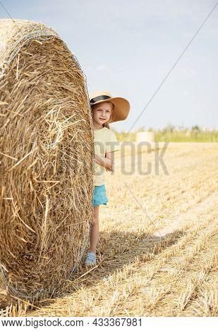 Little Girl Having Fun In A Wheat Field On A Summer Day.