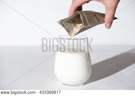 Hand Holding Collagen Powder Travel Pack And Adding It To A Milk To Make Protein Cocktail. Collagen