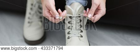 Woman Tying Shoelaces On White Warm Shoes Closeup