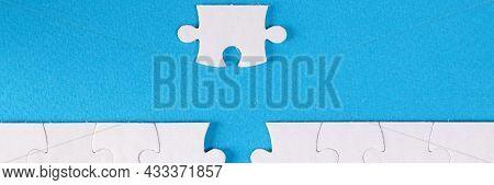 Unfinished White Puzzle Lying Near Last Piece On Blue Background Closeup
