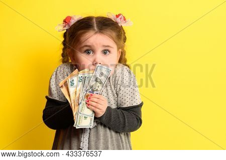 Girl With Banknotes In Hands On A Yellow Background, Business Child With World Currency.