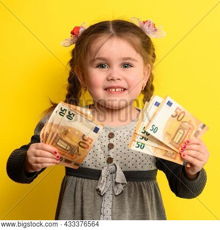 Non-child Saving Money In Children's Hands, Yellow Background And Money With Baby.