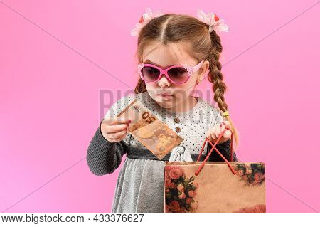 Little Cute Girl On A Pink Background With A Bag And Money, The Theme Of Shopping With Children.