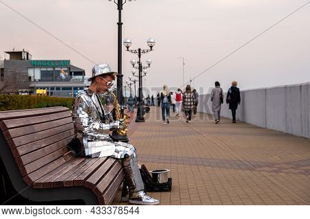 Street Musician Plays The Saxophone. Embankment During The Day. Mirrored Clothes And Mirrored Hat Ad