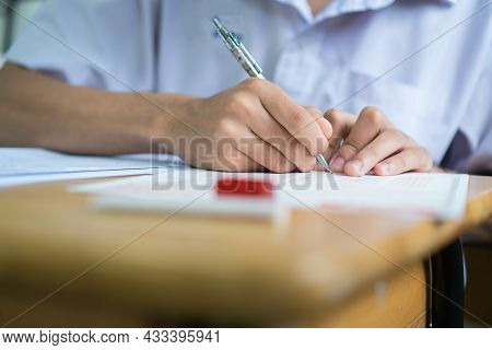 Writing Test In Exam Asian Students Concentrate In High School, Serious Taking Final Examination Des