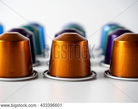 Aluminum Capsules With Aromatic Ground Coffee Are Lined Up On A White Background. Capsules Going Int