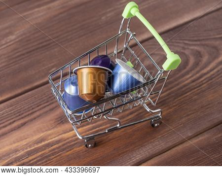 A Small Grocery Cart Full Of Colored Aluminum Capsules With Aromatic Ground Coffee. Modern Technolog
