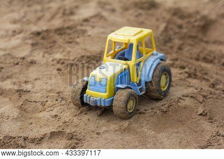 Children's Toy Tractor On The Sandbox.a Forgotten Toy