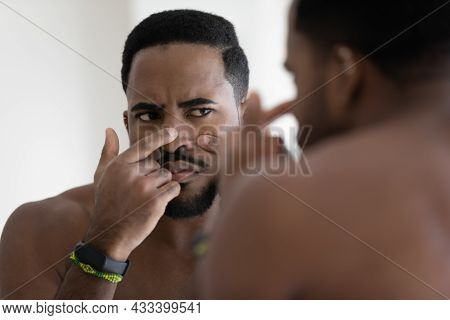 African Guy Looks In Mirror Touch Face Squeezes Pimple